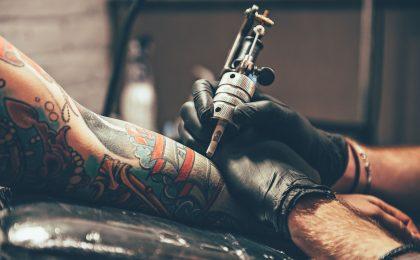 Bild på tatueringsnål och underarm.